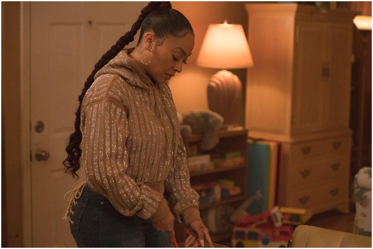 L'acteur de 'The Chi' et 'Power' La La Anthony regardant vers le bas tout en portant un pull et un jean.