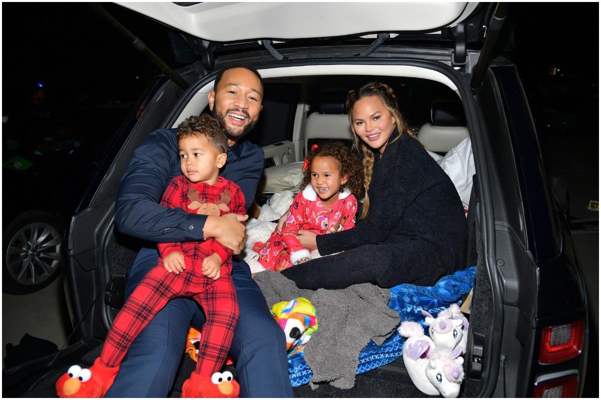 Chrissy Teigen, John Legend et leurs enfants Miles et Luna assis dans le coffre d'une voiture en pyjama.