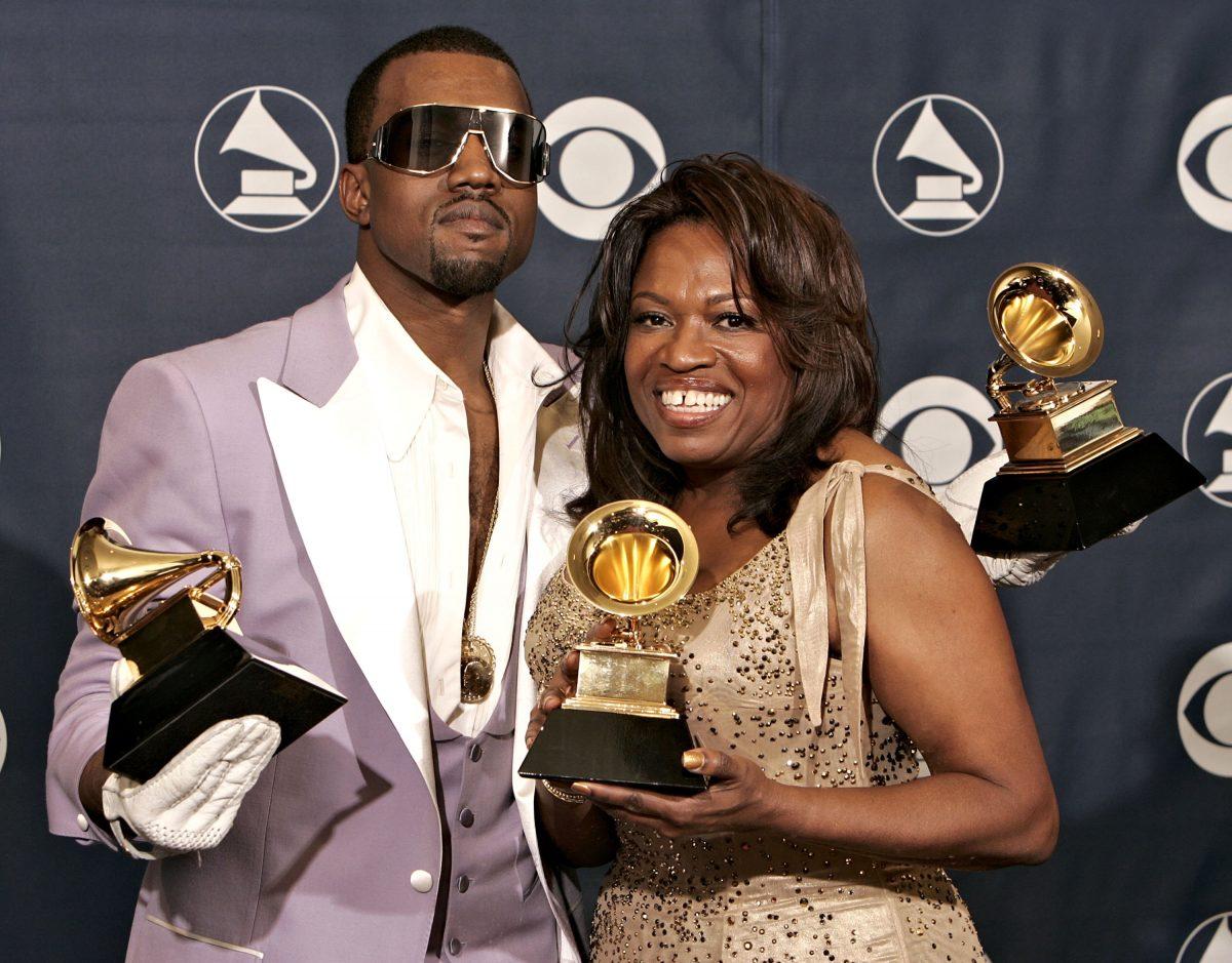 Kanye West et sa maman, Donda, tenant ses trois Grammy Awards tout en souriant à la caméra sur le tapis rouge.