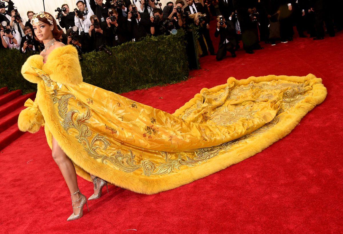 Rihanna posant dans une robe jaune au Met Gala 2019.