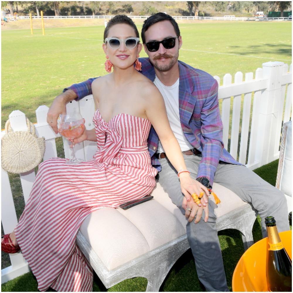 Kate Hudson et Danny Fujikawa assistant à la huitième édition annuelle du Veuve Clicquot Polo Classic vêtus d'une robe à rayures et d'un blazer à motifs.