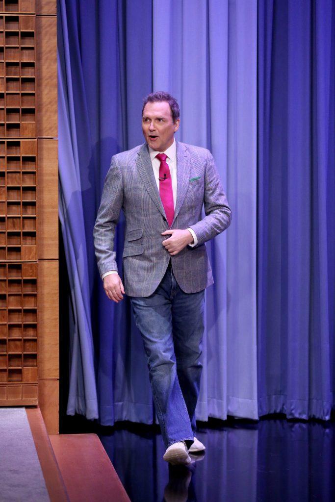 'SNL' alun et acteur Norm Macdonald marchant sur scène dans un blazer et un jean.