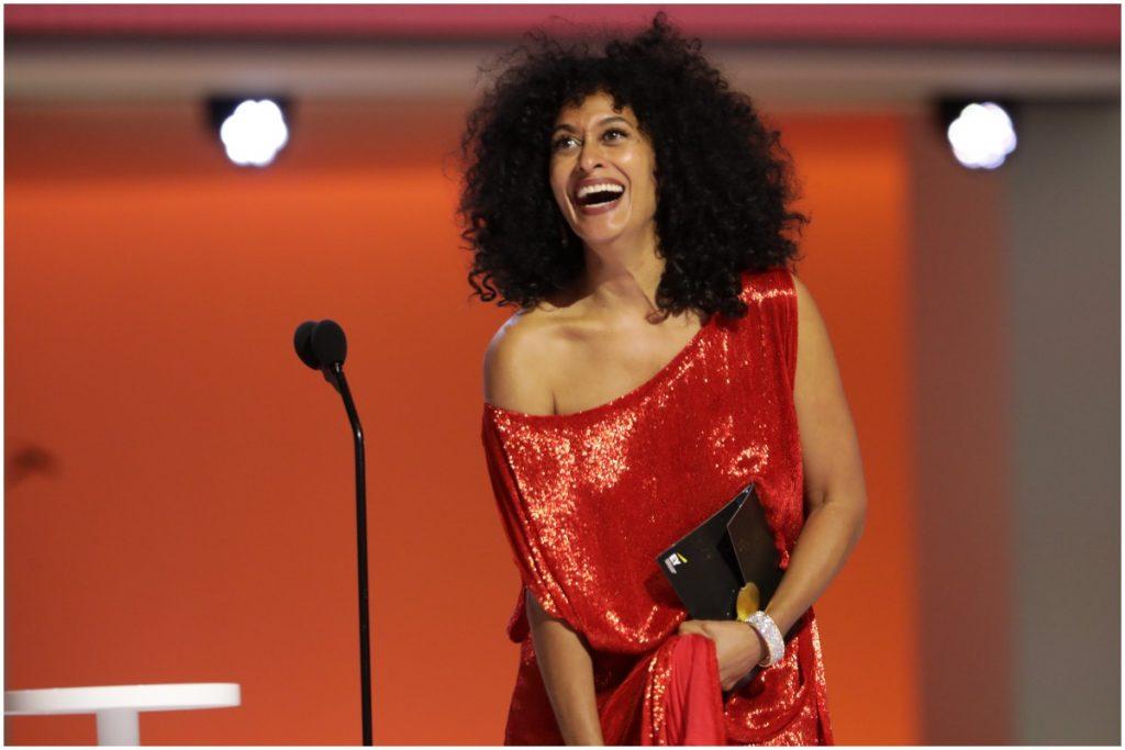 La candidate aux Emmys 2021 Tracee Ellis Ross sourit tout en remettant un prix sur scène.