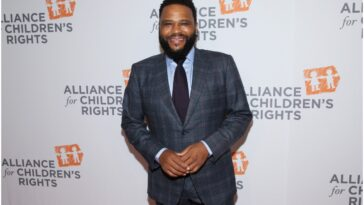 Anthony Anderson standing on the red carpet smiling.