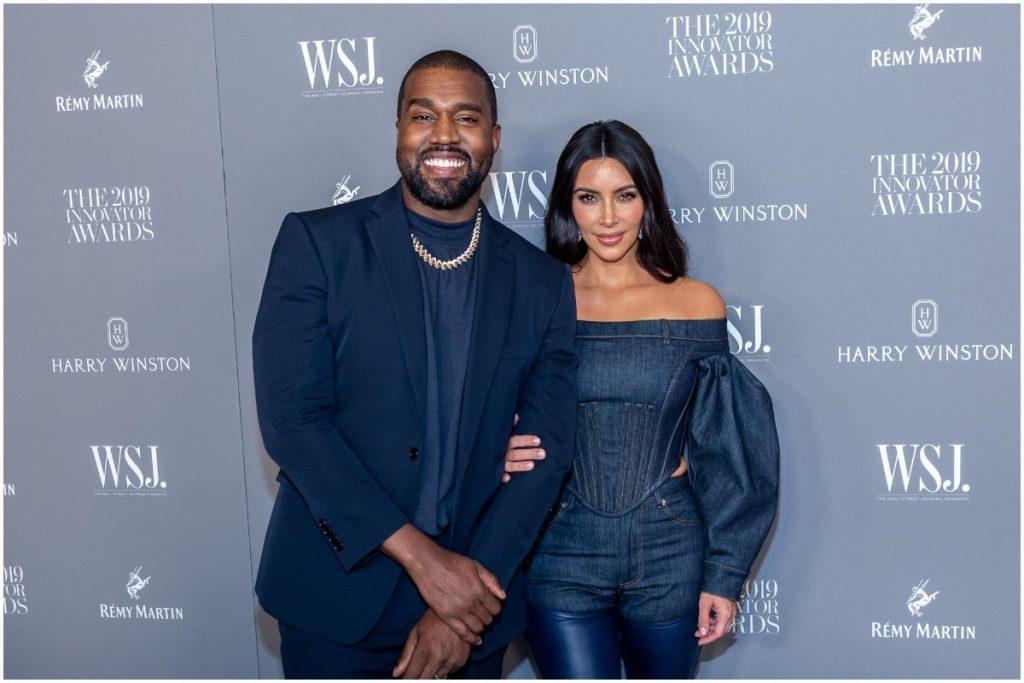 Kanye West et Kim Kardashian s'embrassant et souriant sur le tapis rouge.