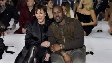 Kris Jenner and boyfriend, Corey Gamble, sitting front row at a fashion show.