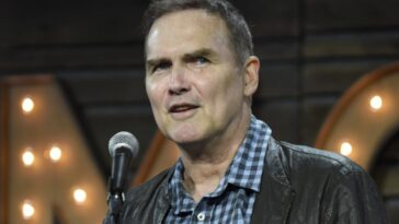 Norm Macdonald looking away from the camera next to a microphone.