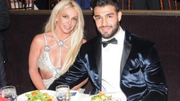 Britney Spears and Sam Asghari smiling and holding hands while sitting down.