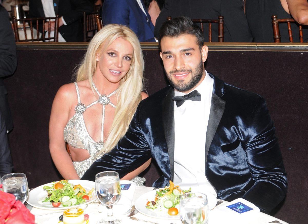 Britney Spears et Sam Asghari souriant et se tenant la main en s'asseyant.