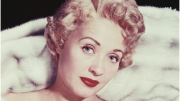 Actor Jane Powell smirking at the camera for a promotional photo shoot.