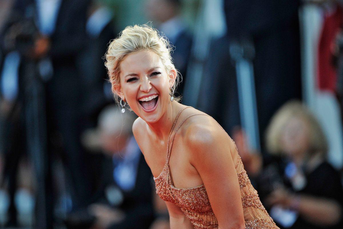 Kate Hudson rayonnante et riant devant la caméra lors d'un événement sur le tapis rouge.